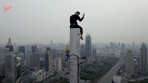 Guy Climbs to Tip of Building