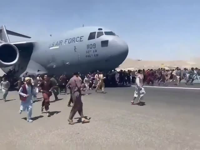 people cling to the landing gear as a C-17 is leaving Afghanistan