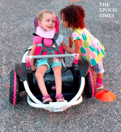 Little Girl Encourages Best Friend to Drive New Motorized Wheelchair
